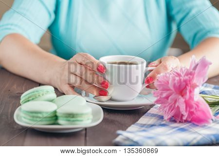 Female hands holding cup of tea with  french macaroons