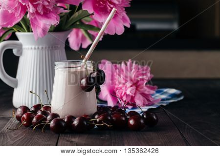 Creamy milk shake with fresh cherries on table
