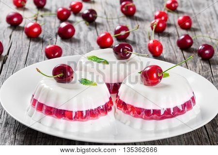 Italian dessert of cherry juice and sweetened cream thickened with gelatin and molded on a white dish on a table napkin with dessert forks and cherries on a dark wooden background close-up