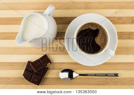 Black Coffee, Chocolate And Jug Of Milk On Striped Table
