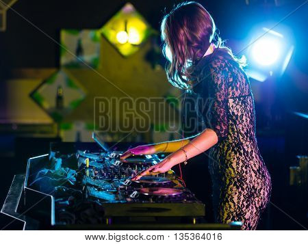 Disc jockey brunette girl mixing electronic music in club
