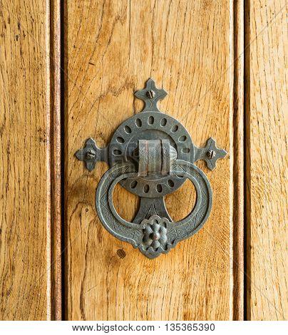 Old Knocker hammered metal door knocker on wooden door.