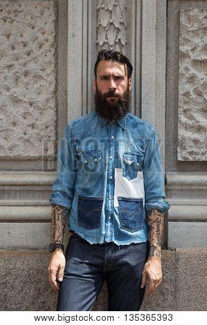 MILAN ITALY - JUNE 19: Fashionable man poses outside Ferragamo fashion show building during Milan Men's Fashion Week on JUNE 19 2016 in Milan.