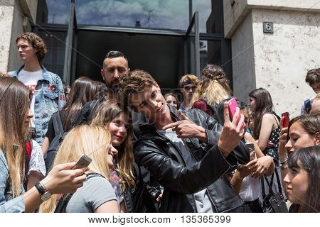 MILAN ITALY - JUNE 19: Beautiful model takes a selfie with some girls outside Ferragamo fashion show building during Milan Men's Fashion Week on JUNE 19 2016 in Milan.