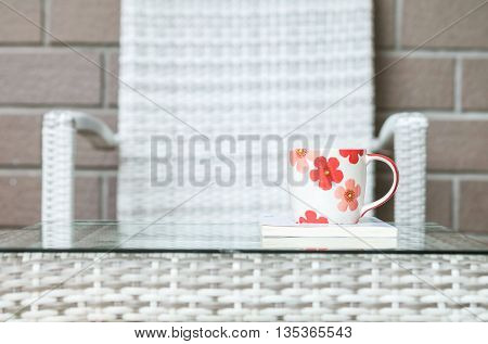 Closeup cute cup on white book on blurred wood weave table and chair textured background