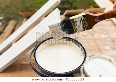 Holding painting brush over the jar with the white paint. Painting timber boards outside with the white paint or white coloured emulsion using 2 inches painting brush.