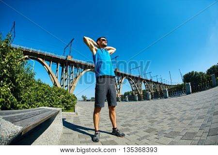 man runner athlete warming up before jogging along a city bay and railroad bridge at the early morning. man fitness sunset jogging workout wellness concept.
