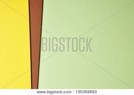 Colored cardboards background in green brown yellow tone. Copy space. Horizontal