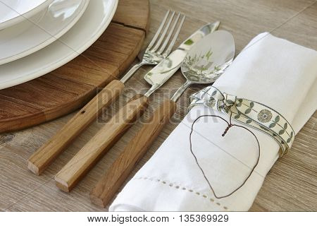 Spoon knife fork and dishware over a rustic table. Horizontal