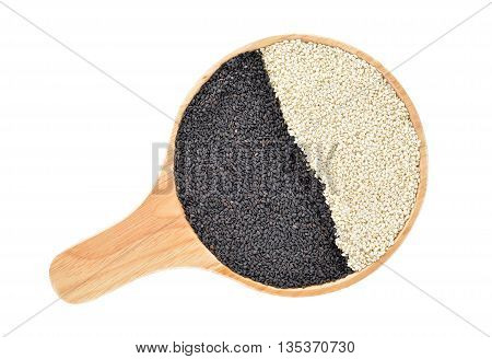 dried black and white sesame in wooden plate with handle on white background