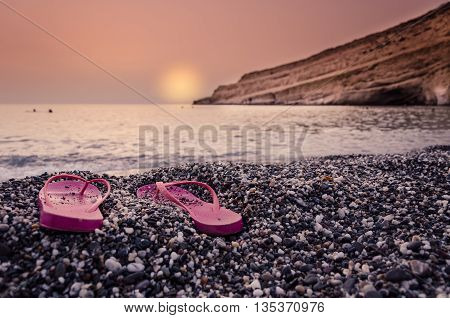 Sunset with woman's  sandals on the beach