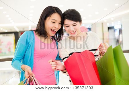 Two women looking inside shopping bag