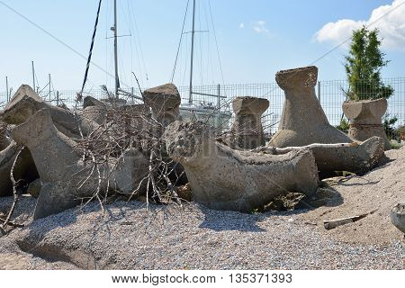 Close Up Of Old And Broken Tetrapods Made Of Concrete Buried In Sand At The Beach, Need To Yacht Har
