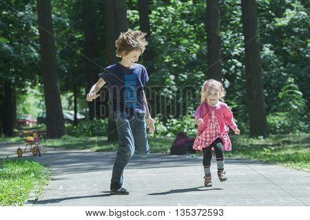Laughing sibling children are playing tag and running on park asphalt footpath