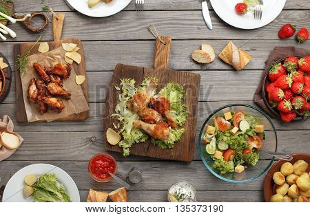 Outdoors Food Concept. On the wooden table different food grilled chicken legs buffalo wings chips bread salad potatoes and strawberry