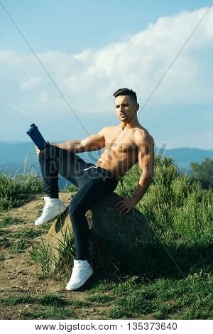 Young sexy man with muscular sexy body and bare torso with chest sitting outdoor with water bottle on sky natural background