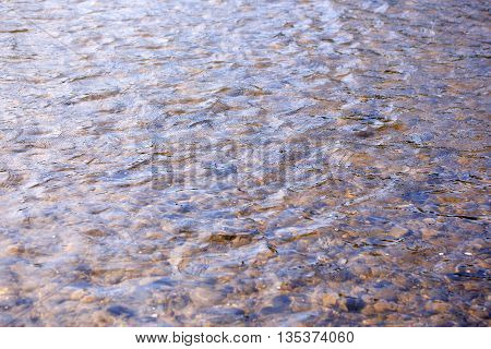 Brown stones and pebbles in clean river water natural background