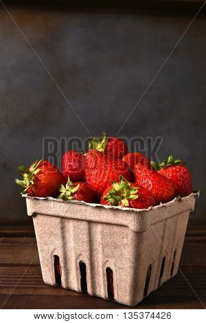 Still life of a cardboard produce container full of fresh picked strawberries on a wood table. Vertical format with copy space.