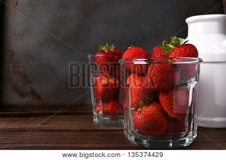 Horizontal still life with copy space of a glass filled with fresh picked strawberries on a wood table. In the background is a second glass of berries and a milk can.