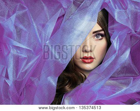 Fashion photo of beautiful women under purple veil. Beauty portrait. Perfect makeup. Eyelashes. Lips. Cosmetic Eyeshadow