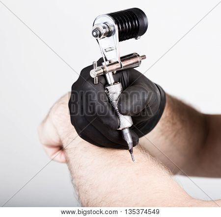 close-up of Tattooist hands in black gloves with tattoo machine.