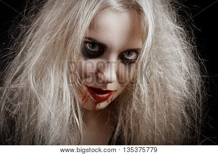 blond bloody witch on black background smiling