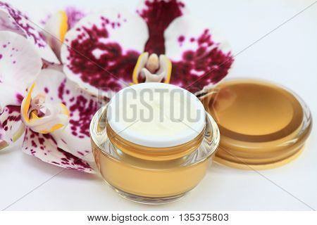 Face and body cream decorated with orchid on white background