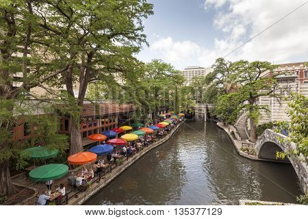 SAN ANTONIO USA - APR 11: The famous San Antonio River Walk and a cafe with colorful umbrellas. April 11 2016 in San Antonio Texas United States