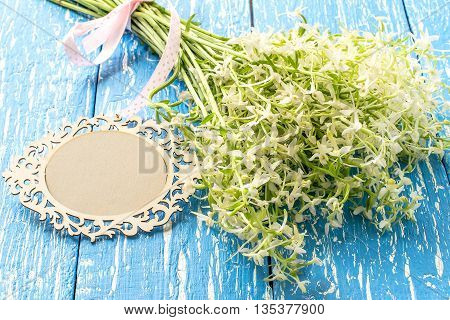 Delicate bouquet of wild orchids also known as Lesser Butterfly Orchid (Platanthera bifolia) and card for your text on a blue wooden table