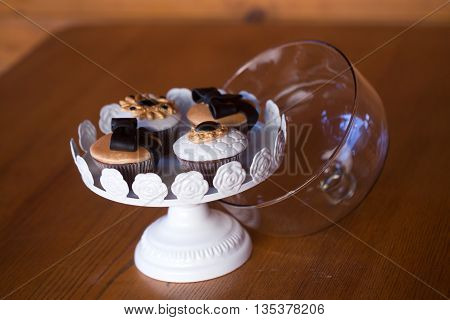 tasty cupcakes in glass vase decorated with chocolate bow and icing on wooden table