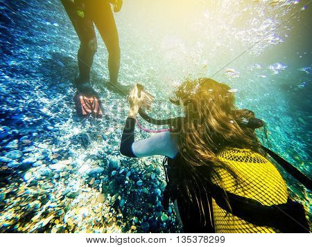 Woman diving close to the ocean floor.