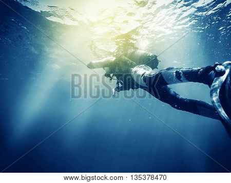 Woman doing scuba diving, floating in the sea surface.