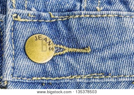 close up of blue jeans with brass studs