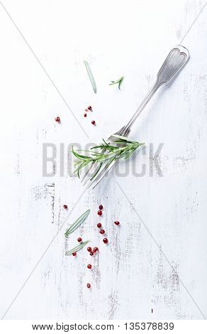 Vintage fork with rosemary and pink peppercorns