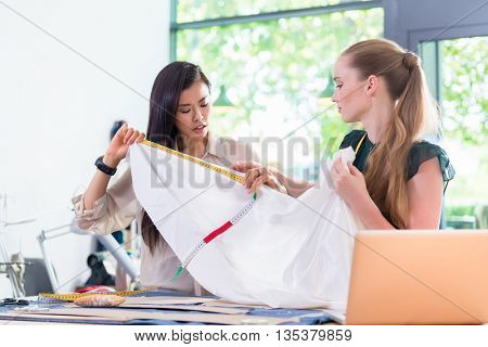 Young Fashion designer women measuring cloth