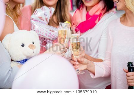 Friends clinking glasses on baby shower party, close-up shot on the sparkling wine