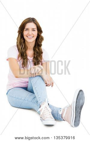 Portrait of happy young woman sitting down and smiling on white background