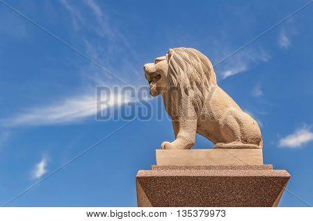 Carved sandstone lion on blue sky background