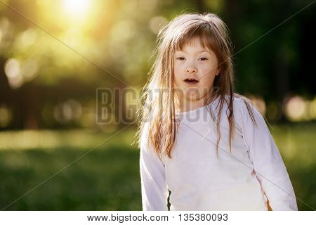 Beutiful happy child suffering from Down syndrome smiling outdoors
