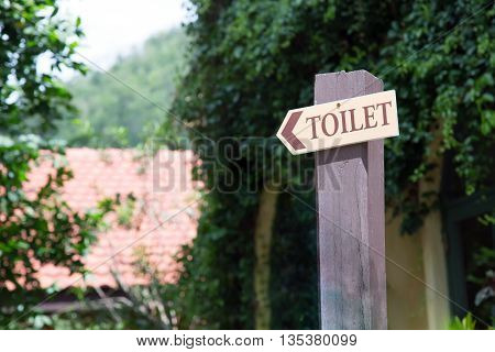 Guide post arrow to toilet on wood column