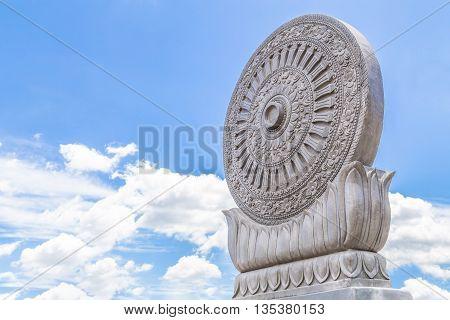 Carved sandstone Dharmachakra on blue sky background