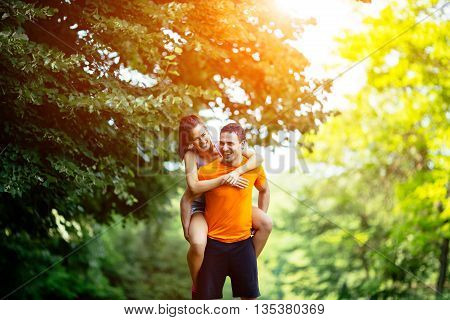 Man carrying woman piggyback after jogging is done