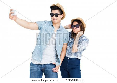 Happy young couple taking a selfie on white background