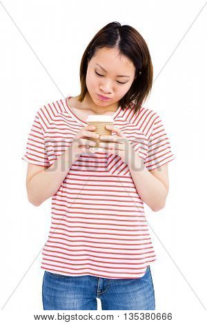 Happy young woman holding disposable coffee cup on white background
