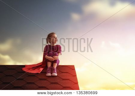 Little child plays superhero. Kig on the background of sunset sky. Girl power concept