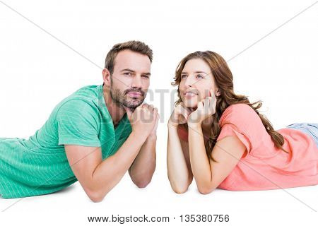 Thoughtful young couple lying on floor looking away on white background