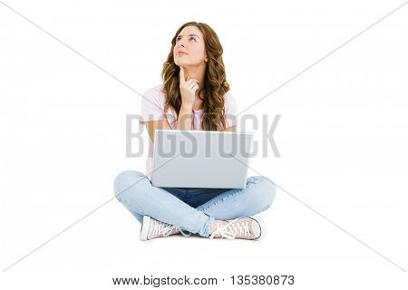 Thoughtful young woman using laptop on white background
