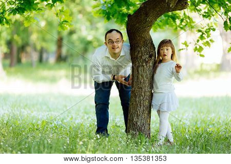 Down syndrome siblings playing outdoors in a park