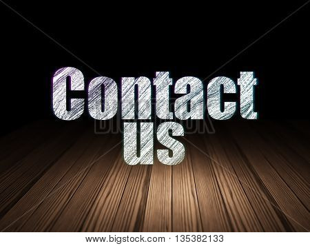 Advertising concept: Glowing text Contact Us in grunge dark room with Wooden Floor, black background