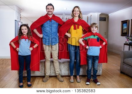 Portrait of family pretending to be superhero in living room at home